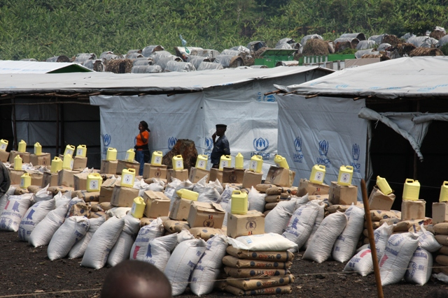 At a camp for displaced people in Democratic Republic of Congo, sacks of grain and jugs of oil await distribution. Photo by Liz Lucas for Oxfam America