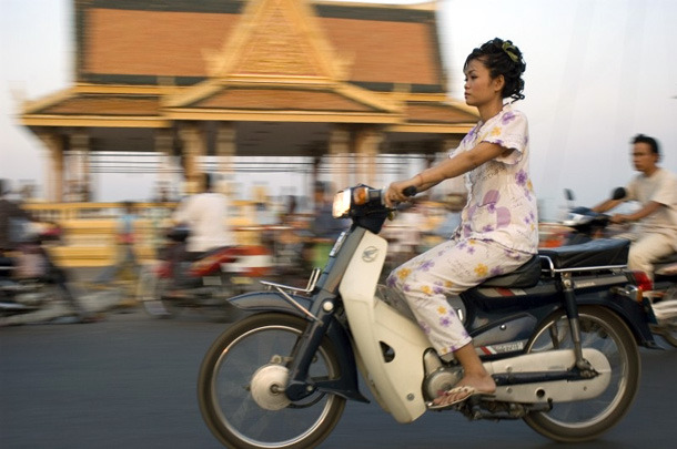A woman rides her motor bike through the crowded streets of Phnom Penh. Photo by Brett Eloff/Oxfam America