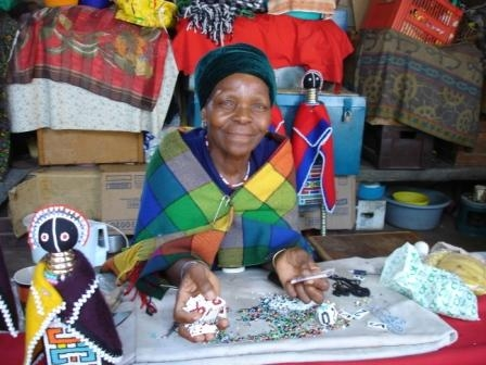 In a market in South Africa, a woman sells pins to commemorate those lost to AIDS. Photo by Emily Farr