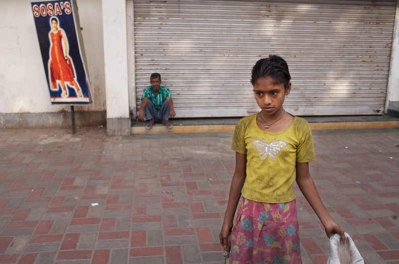 Sahera begins her morning duties as a rag-picker in Lucknow, India, where Oxfam funds a school and health programs for working children. According to Peter Singer, kids—in India and elsewhere—are one of the groups most at risk from poverty-related diseases. Photo: Tom Pietrasik / Oxfam