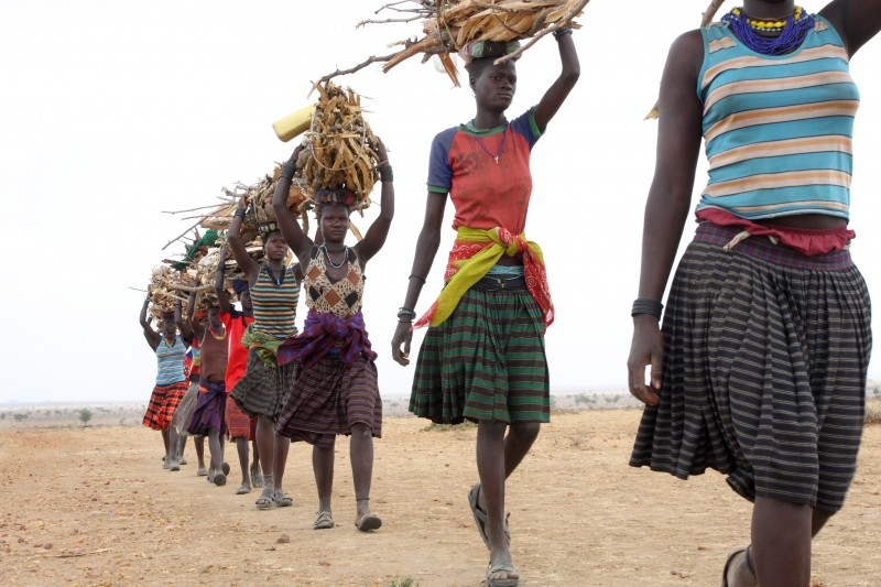 "Women carry firewood back to their home village of Caicaoan, Uganda. The women place a cushioning loop of cloth on their heads, and then help each other to lift and balance the heavy loads. ""We travel further and further for firewood every year, and it takes us to less safe places,"" says Martina Longom, a Caicoan woman and one of Oxfam's Sisters on the Planet (Go to www.oxfamamerica.org/sisters to hear her story.) Photo: Geoff Sayer / Oxfam"