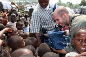 Oxfam America videographer Rob Baker shows some children in an IDP camp the screen on his camera.
