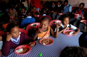 Children get lunch after school in Soweto, South Africa. Programs like this serving orphans and vulnerable children are essential, but must be matched with efforts to create laws and policies that will help reduce the spread of HIV and AIDS. Photo by Brett Eloff/Oxfam America.