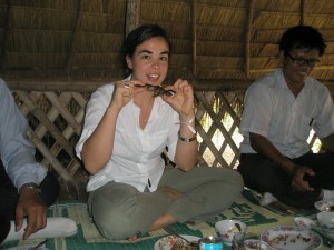 Clara Herrero, program assistant at Oxfam America, decides that when in Cambodia, she should do as the Cambodians do. Here, she's about to take a bite out of a crispy frog.