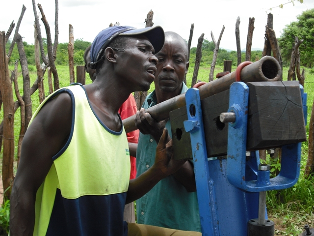 Villagers work on repairing a broken well, known as a bore hole, in the Mudzi district of Zimbabwe.