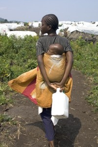 A woman and a baby walk back to a camp for displaced people in Democratic Republic of Congo.